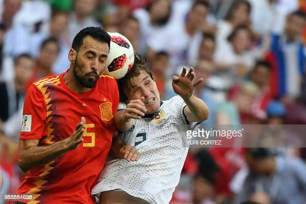 TOPSHOT Spain's midfielder Sergio Busquets heads the ball with Russia's defender Mario Fernandes during the Russia 2018 World Cup round of 16...