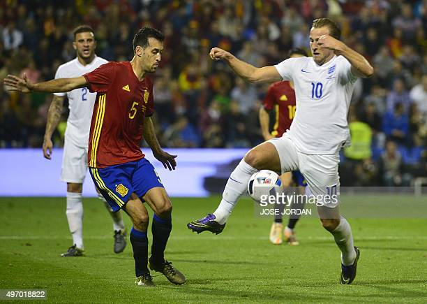 Spain's midfielder Sergio Busquets vies with England's forward Harry Kane during the friendly football match Spain vs England at the Jose Rico Perez...