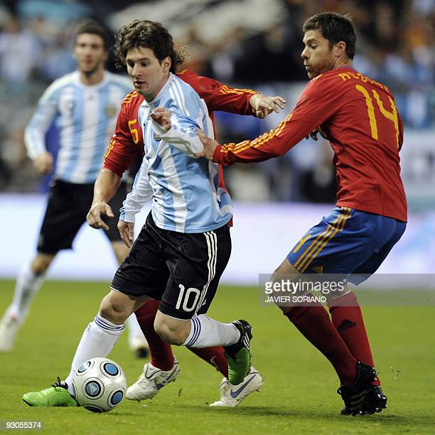 Spain's midfielder Xabi Alons vies for the ball with Argentina's Lionel Messi during a friendly football match at the Vicente Calderon stadium in...