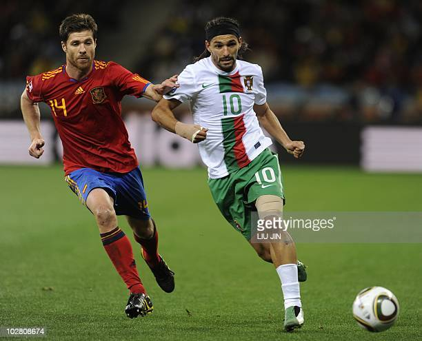 Spain's midfielder Xabi Alonso fights for the ball with Portugal's striker Danny during the 2010 World Cup round of 16 match Spain versus Portugal on...