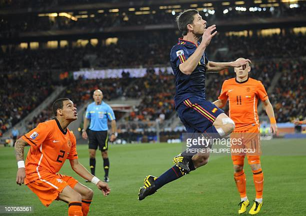 Spain's midfielder Xabi Alonso jumps for the ball ahead of Netherlands' defender Gregory van der Wiel during the 2010 World Cup football final...