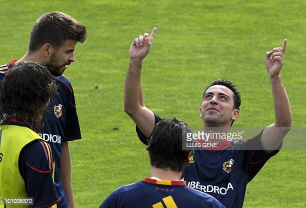 Spain's midfielder Xavi Hernandez jokes with Spain's defender Gerard Pique before a training session of the Spanish football team on May 27 at the...