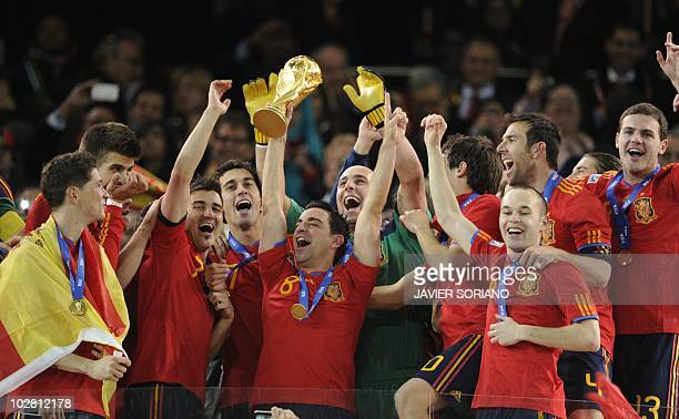 Spain's midfielder Xavi holds the trophy as Spain's midfielder Andres Iniesta gestures during the award ceremony following the 2010 FIFA football...