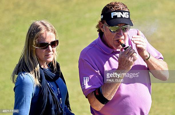 Spain's Miguel Angel Jimenez smokes a cigar on the fourth tee with his wife Susanna Styblo at Royal Liverpool Golf Course in Hoylake northwest...