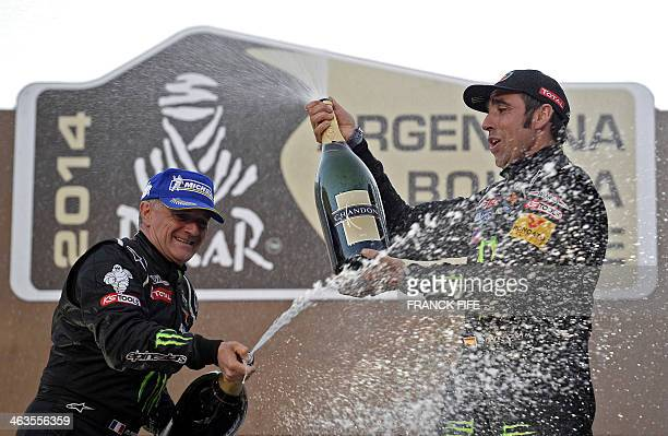 Spains Nani Roma celebrates with codriver Michel Perin on the podium of the 2014 Rally Dakar in Valparaiso Chile on January 18 2014 Spains Nani Roma...