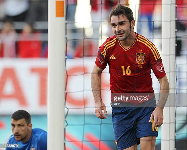 Spain's national football team player Adrian Lopez reacts after scoring a goal as Serbia's national football team goalkeeper Damir Kahriman on during...