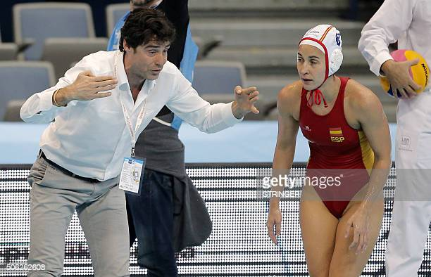 Spain's national water polo team head coach Miguel Oca speaks with Maria Pena Del Pilar during the women's water polo bronze medal match between...