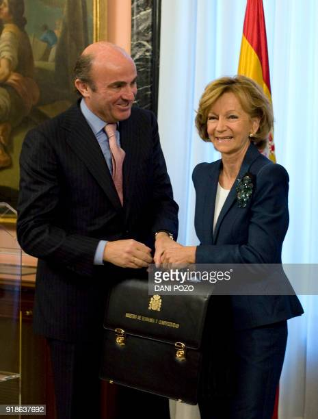 Spain's new Minister of Economy and Competitiveness Luis de Guindos poses holding his new briefcase next to former Economy Minister Elena Salgado at...