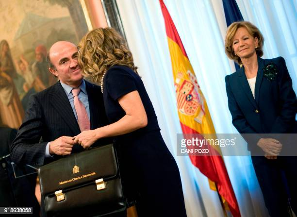 Spain's new Minister of Economy and Competitiveness Luis de Guindos receives his new briefcase from former Science Minister Elena Garmendia next to...