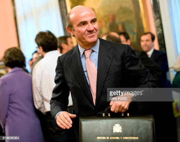 Spain's new Minister of Economy and Competitiveness Luis de Guindos poses holding his new briefcase at the Ministry of Economy on December 22 2011 in...