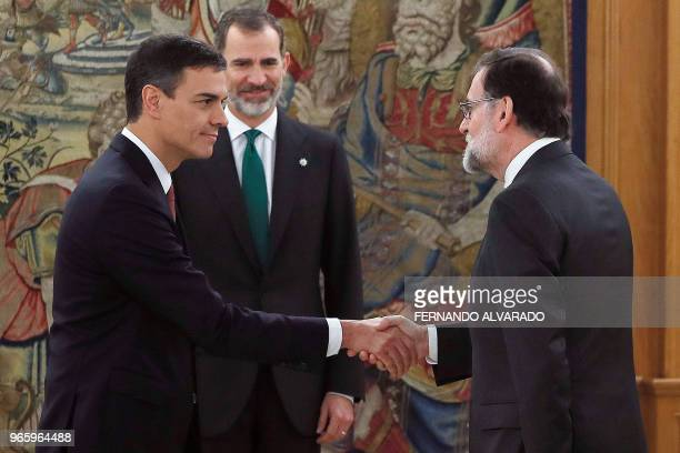 TOPSHOT Spain's new Prime Minister Pedro Sanchez shakes hands with outgoing premier Mariano Rajoy next to Spain's King Felipe VI during a swearingin...