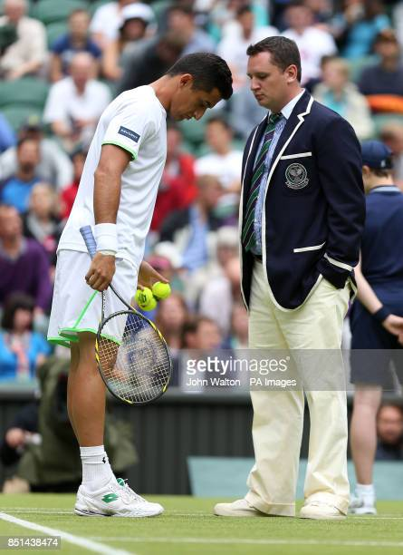 Spain's Nicolas Almagro speaks with umpire Jake Garner as rain delays play on Centre Court during day five of the Wimbledon Championships at The All...