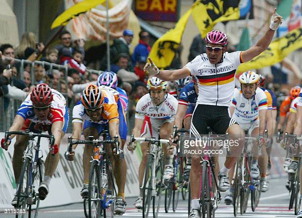 Spain's Oscar Gomez Freire crosses the finish line and wins the 95th edition of MilanSan Remo cycling race as Germany's Erik Zabel raises his arms in...