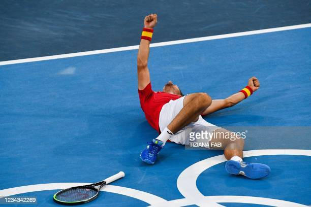 Spain's Pablo Carreno Busta celebrates after defeating Serbia's Novak Djokovic during their Tokyo 2020 Olympic Games men's singles tennis match for...