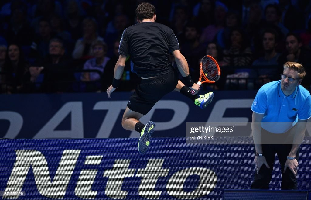 Spain's Pablo Carreno Busta hurdles the advertising hoardings after chasing the ball to play a shot against Austria's Dominic Thiem during their men's singles round-robin match on day four of the ATP World Tour Finals tennis tournament at the O2 Arena in London on November 15 2017. / AFP PHOTO / Glyn KIRK