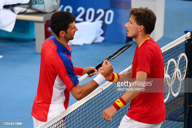 Spain's Pablo Carreno Busta shakes hand with Serbia's Novak Djokovic after winning the Tokyo 2020 Olympic Games men's singles tennis match for the...