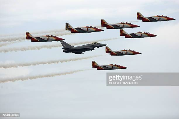 Spain's patrulla aguila or Eagle patrol escort a Eurofighter during the Torre del Mar International Air Festival in Torre del Mar near Malaga on July...