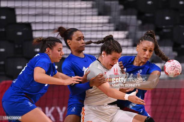 Spain's pivot Ainhoa Hernandez Serrador is challenged by France's pivot Beatrice Edwige and France's left wing Allison Pineau during the women's...