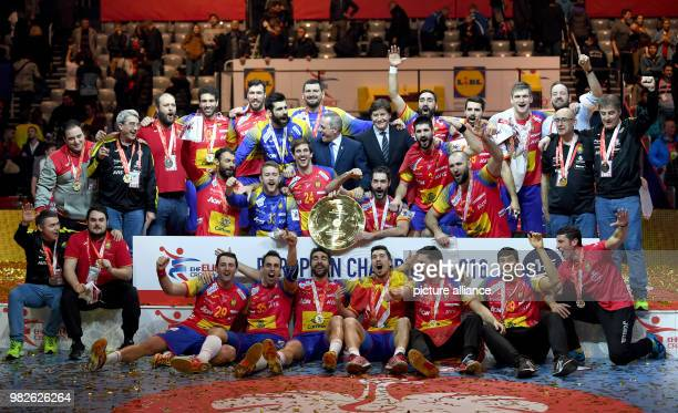 Spain's players and other team members cheer with the trophy during the award ceremony after the finale at the Handball European Championship in...