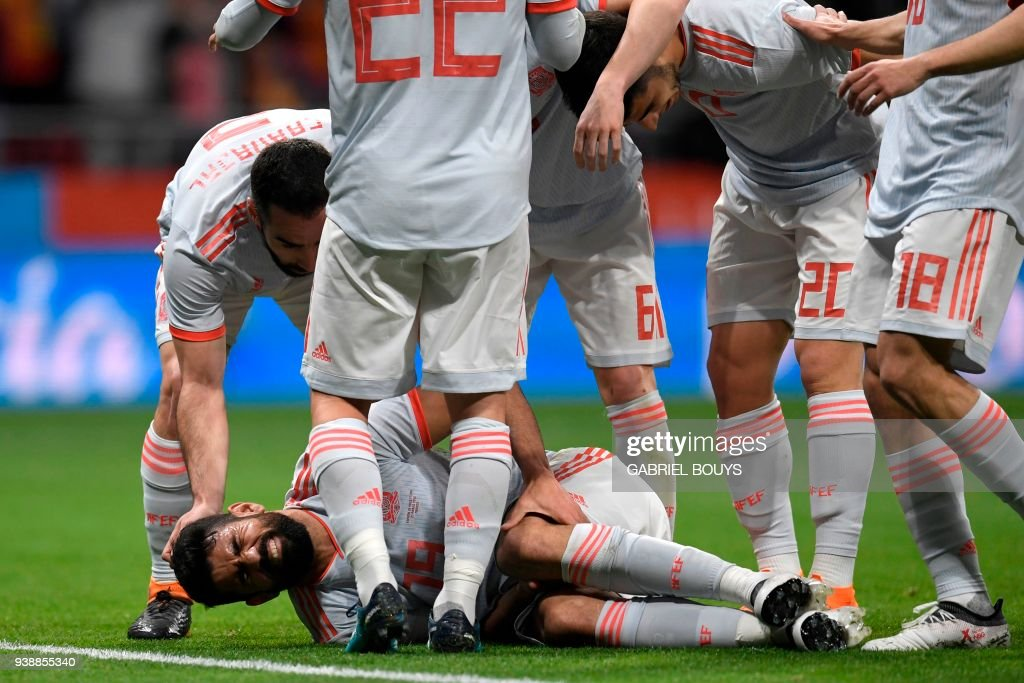 Spain's players celebrate with forward Diego Costa (bottom) as he reacts in pain after getting injured while scoring a goal during a friendly football match between Spain and Argentina at the Wanda Metropolitano Stadium in Madrid on March 27, 2018. /
