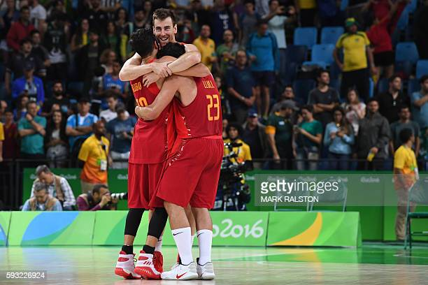 Spain's point guard Ricky Rubio Spain's small forward Victor Claver and Spain's guard Sergio Llull celebrate after winning a Men's Bronze medal...