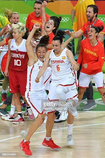Spain's point guard Silvia Dominguez and Spain's point guard Laia Palau and Spain's players celebrate after defeating Turkey as Turkey's point guard...
