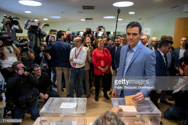 Spain's Prime Minister and Spanish Socialist Workers' Party leader Pedro Sanchez poses for photographers as he casts his vote at a polling station...
