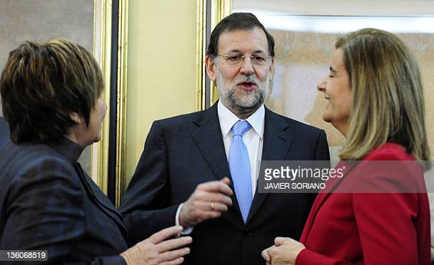 Spain's Prime Minister Mariano Rajoy chats with Spain's Minister of Employment and Social security Maria Fatima Banez Garcia and Partido Popular's...