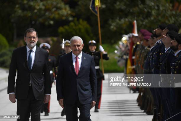 Spain's Prime Minister Mariano Rajoy reviews the honor guard with Turkish Prime Minister Binali Yildirim at La Moncloa palace in Madrid on April 24,...