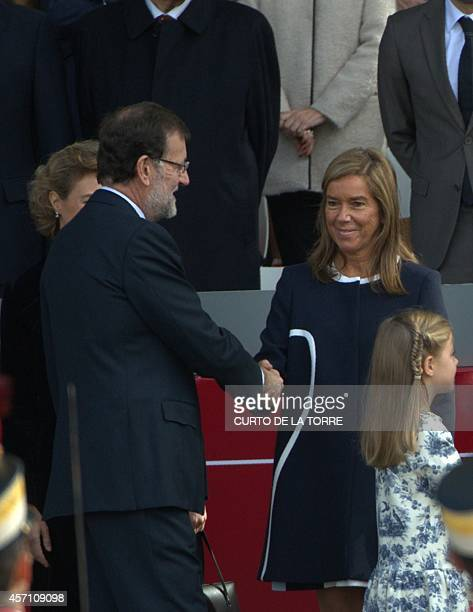Spain's Prime Minister Mariano Rajoy shakes hands with Spanish Minister of Health Ana Mato during the Spanish National Day military parade in Madrid...