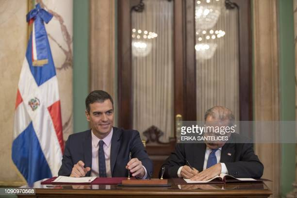 Spain's Prime Minister Pedro Sanchez and Dominican President Danilo Medina sign an agreement during a meeting at the National Palace in Santo Domingo...
