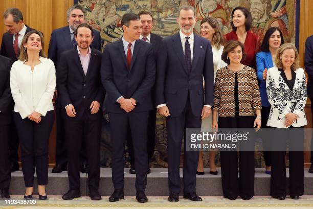 Spain's Prime Minister Pedro Sanchez and Spanish King Felipe VI pose with newly appointed ministers of the new coallition goverment during a ceremony...