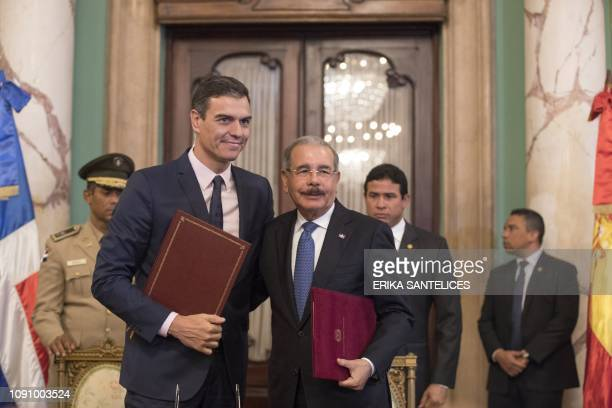 Spain's Prime Minister Pedro Sanchez poses next to Dominican President Danilo Medina after they sign an agreement during a meeting at the National...