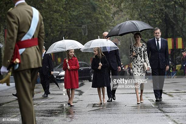 Spain's princess Sofia princess Leonor Spain's Queen Letizia and Spanish Prime Minister Mariano Rajoy walk in the rain during the Spanish National...