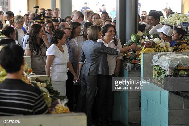 Spain's Queen Letizia extends her hand to a vendor at a market in Suchitoto 47 km east of San Salvador on May 27 2015 Queen Letizia visits El...
