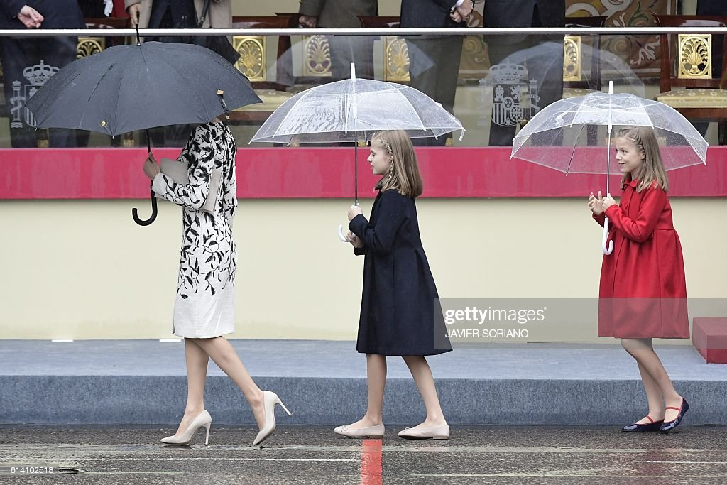 TOPSHOT - (L to R) Spain's Queen Letizia, Spain's princess Sofia, and princess Leonor walk after the Spanish National Day military parade in Madrid on October 12, 2016. / AFP / JAVIER
