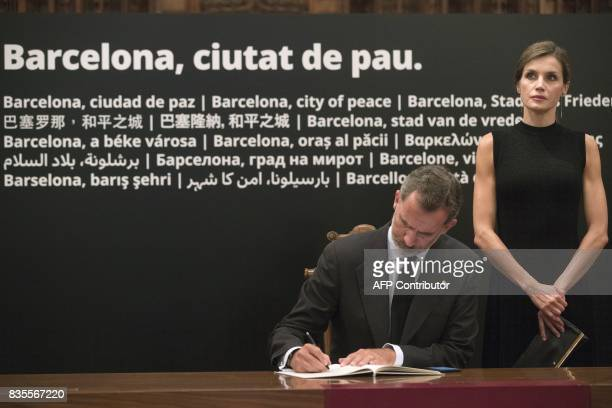 Spain's Queen Letizia stands next to Spanish king Felipe VI signing the condolences book for the victims of the Barcelona and Cambrils attacks in the...