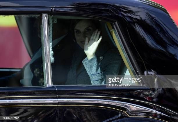 Spain's Queen Letizia waves from a car as she leaves with her husband the king after attending the Spanish National Day military parade in Madrid on...