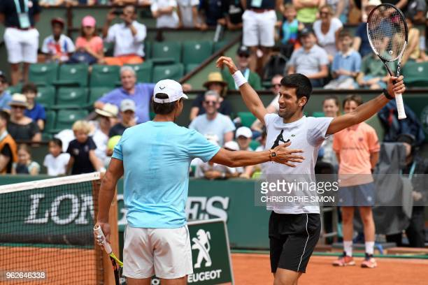Spain's Rafael Nadal and Serbia's Novak Djokovic hug during an exhibition game during 'Kids Day' on The Philippe Chatrier Court in Paris on May 26 on...