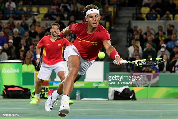 Spain's Rafael Nadal and Spain's Marc Lopez return the ball to Romania's Florin Mergea and Romania's Horia Tecau during their men's doubles final...