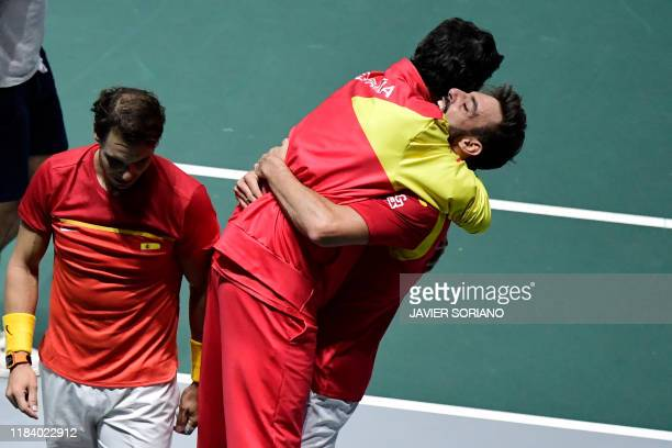Spain's Rafael Nadal and Spain's Marcel Granollers celebrate with Spain's captain Sergi Bruguera after winning the doubles quarter-final tennis match...