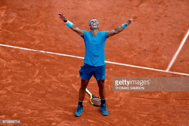 TOPSHOT Spain's Rafael Nadal celebrates after victory over Austria's Dominic Thiem after their men's singles final match on day fifteen of The Roland...