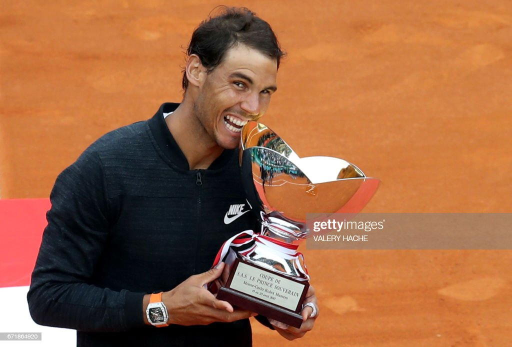 Spain's Rafael Nadal celebrates and bites the trophy during the prize ceremony after winning the Monte-Carlo ATP Masters Series Tournament final tennis match, on April 23, 2017 in Monaco. /