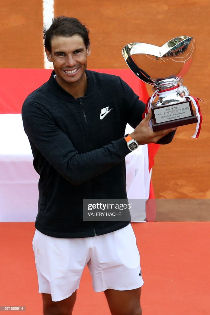 Spain's Rafael Nadal celebrates as he holds the trophy during the prize ceremony after winning the Monte-Carlo ATP Masters Series Tournament final tennis match, on April 23, 2017 in Monaco. /