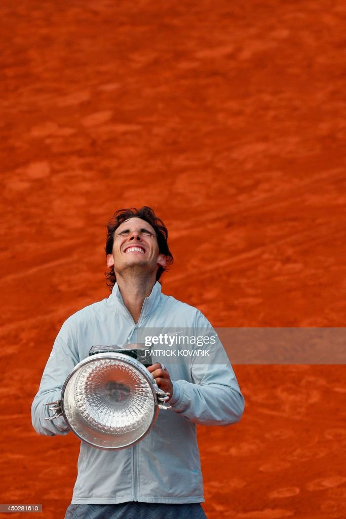 Spain's Rafael Nadal celebrates with the Musketeers trophy after winning the French tennis Open men's final match against Serbia's Novak Djokovic at the Roland Garros stadium in Paris on June 8, 2014. AFP PHOTO / PATRICK KOVARIK / AFP PHOTO / Patrick KOVARIK