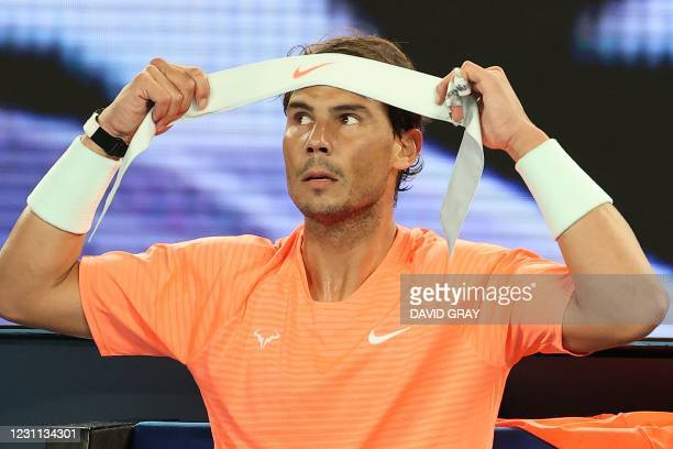 Spain's Rafael Nadal changes his headband between the games against Britain's Cameron Norrie during their men's singles match on day six of the...