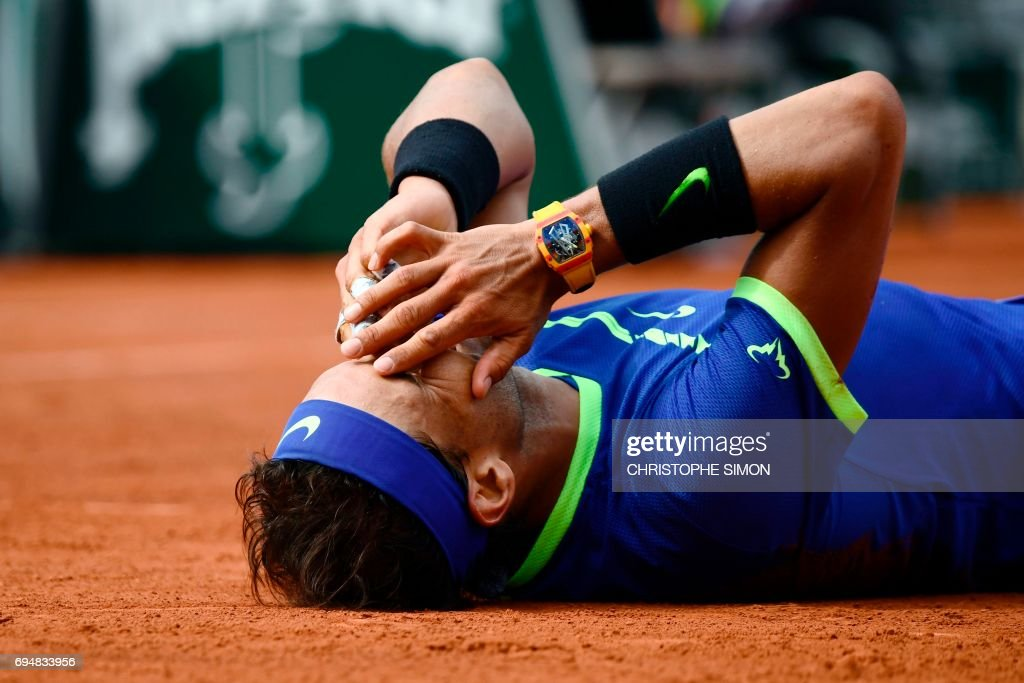 TOPSHOT - Spain's Rafael Nadal falls to the court as he celebrates after winning the men's final tennis match against Switzerland's Stanislas Wawrinka at the Roland Garros 2017 French Open on June 11, 2017 in Paris. /