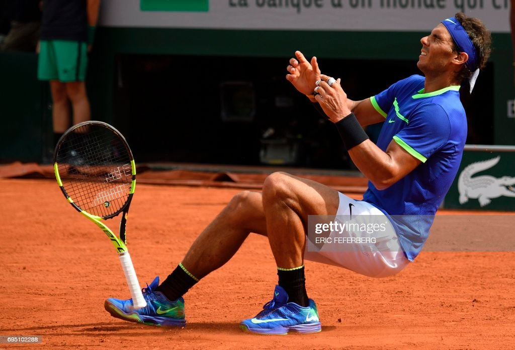 Spain's Rafael Nadal falls to the court as he celebrates after winning the men's final tennis match against Switzerland's Stanislas Wawrinka at the Roland Garros 2017 French Open on June 11, 2017 in Paris. /