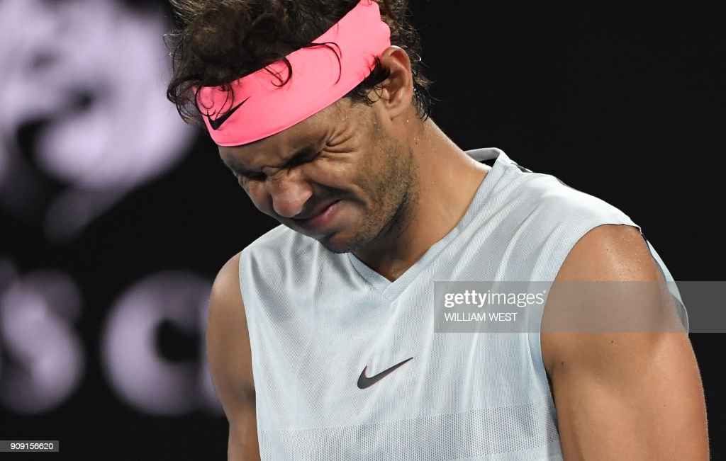 TOPSHOT - Spain's Rafael Nadal grimaces as he walks on court while preparing to serve to Croatia's Marin Cilic during their men's singles quarter-finals match on day nine of the Australian Open tennis tournament in Melbourne on January 23, 2018. World No.1 Rafael Nadal retired with a leg injury handing Marin Cilic passage into his second Australian Open semi-final. /