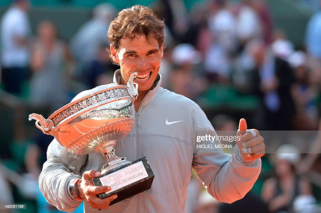 Spain's Rafael Nadal holds the Musketeers trophy after winning the French tennis Open men's final match against Serbia's Novak Djokovic at the Roland Garros stadium in Paris on June 8, 2014. AFP PHOTO / MIGUEL MEDINA / AFP PHOTO / Miguel MEDINA